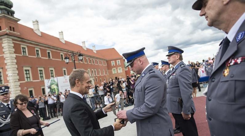 Premier wręcza statuetkę konkursową st. sierż. Damianowi Ciećwierzowi